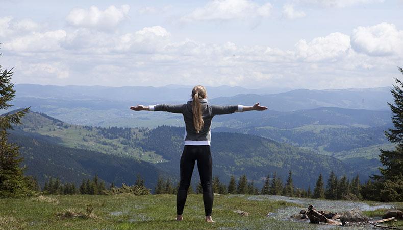 頂上で手を広げる女性