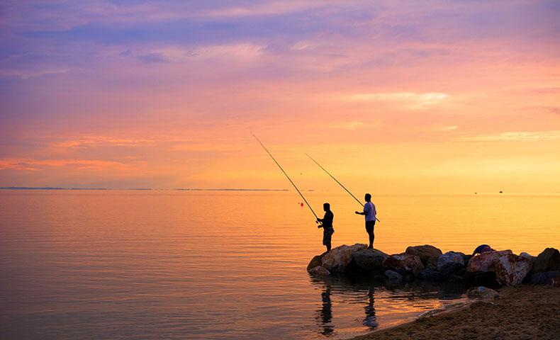 夕陽をバックに釣りをする人たち